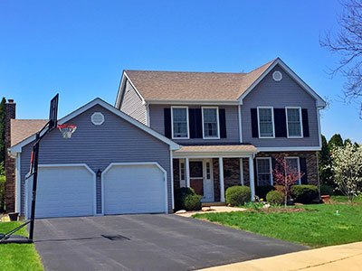 Average sized home with blue painted siding, basketball free standing basket, stone decor on the front walls, and clean landscape.