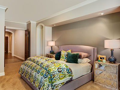 Small bedroom with beige painted walls, light brown leather bed, colorful sheets, warm lighting, and hallway entrance.