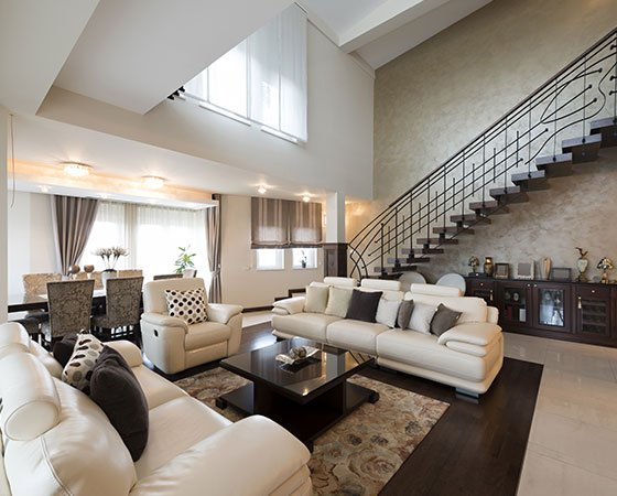 Modern living room with beige painted walls, dark brown couch, open space kitchen and dining area, warm lighting, and big glass doors.