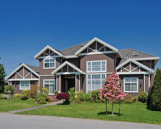 Large house with chocolate brown painted siding, white windows, and front yard landscaping.