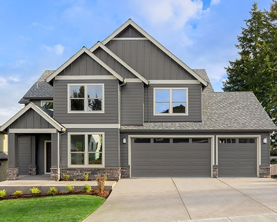 Home exterior with dark gray painted siding, clean landscape, and sunny sky.