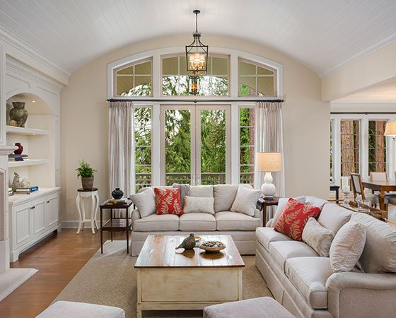 Home interior with beige painted walls, white painted wooden ceiling, white furniture, and beige carpet and couch.