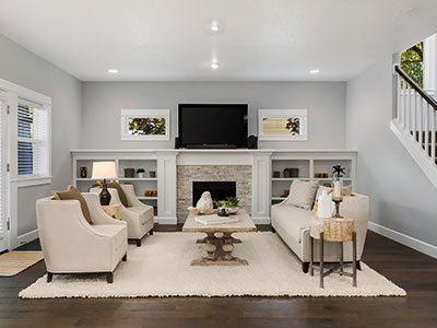Small living room with light gray painted walls, light beige couch and carpet, stone chimney, flat screen TV, and stairs on the right side.