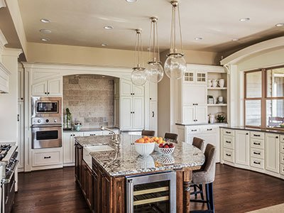 Luxury kitchen with large, brown island, quartz countertop, silver finish appliances, and white painted cabinets.