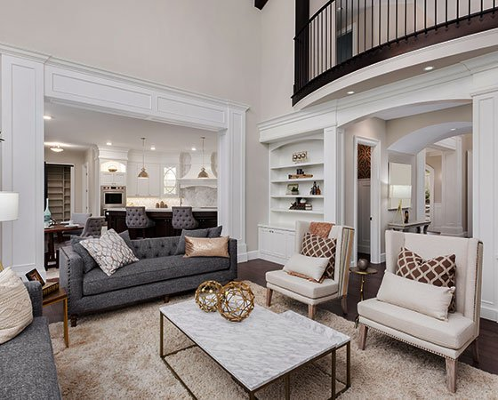 Living room with a gray couch, beige carpet, two white chairs, a marble coffee table, and white furniture.
