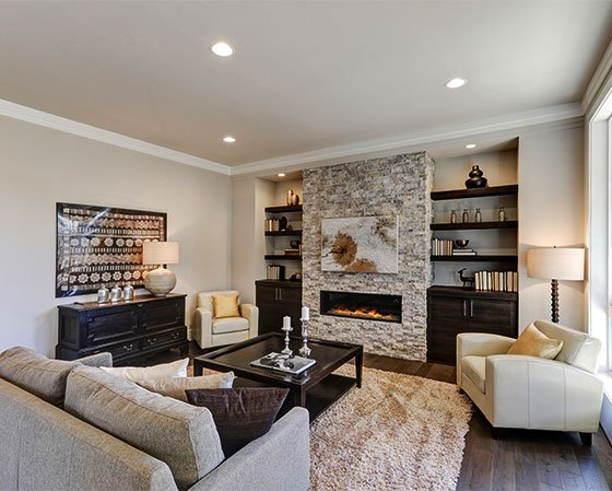 Living room with light gray painted walls, stone chimney, dark wood furniture, gray couch, and beige carpet.