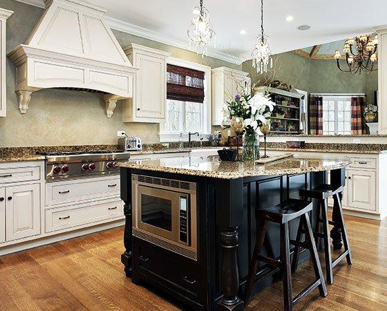 Modern, elegant kitchen with white cabinets, silver finish appliances, dark wooden island, and beige quartz countertop.