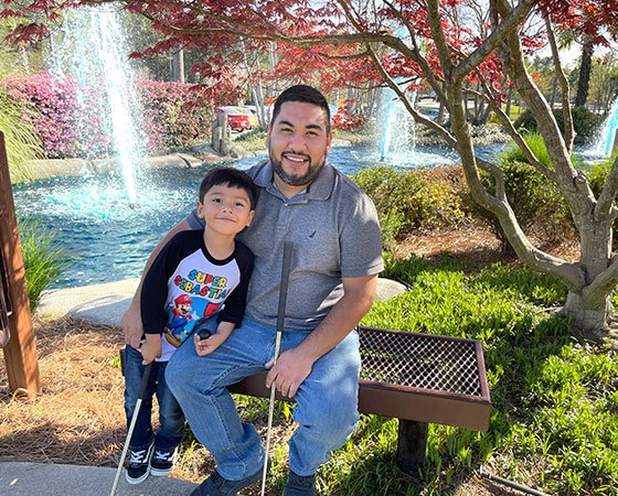 Owner and his son sitting on a metal bench in the park, with waterfall behind.