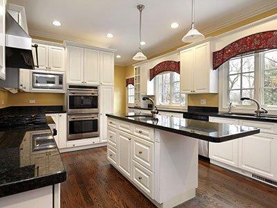 Average sized kitchen with white cabinets, dark brown island, warm lighting, and dark wooden flooring.